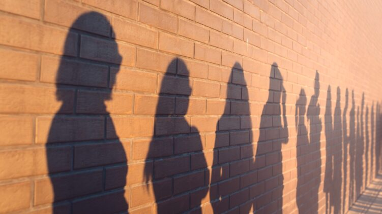 a line of shadows of people lined up against a red brick wall. Stand in a queue to the changes.